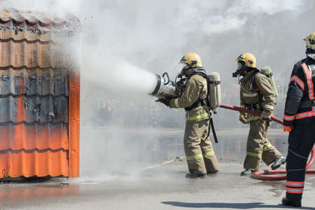 Group of firefighters extinguishing fire from fire hose, using firefighting water-foam barrel with air-mechanical foam during professional holiday Firefighters Day. Kamchatka, Russia - April 27, 2019.