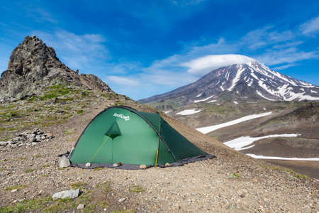 Green tourist tent Red Fox for travel and camping standing in mountain on background of volcanic landscape - cone of Koryakskaya Sopka, blue sky with clouds. Kamchatka Peninsula, Russia - Aug 19, 2015
