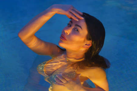 Glamorous brunette in swimsuit swims in geothermal water in pool at spa, looking at camera. Womans curvy body is illuminated under water by night lights in pool. Soft selective focus on models eyes. Stockfoto