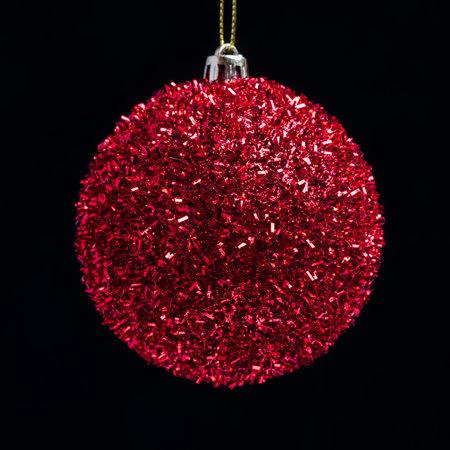 Shining red X-mas ball on black background
