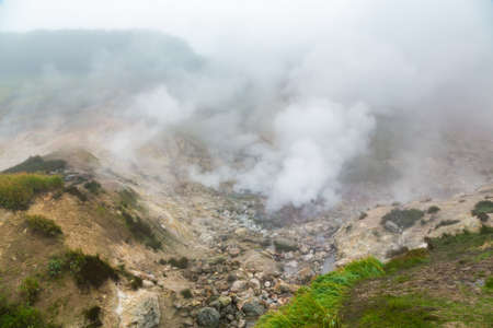 Mysterious view of volcanic landscape, aggressive hot spring, erupting fumarole, gas-steam activity in crater of active volcano Stockfoto