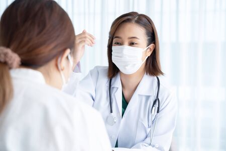 The doctor asks about the symptoms of patients in the examination room.
