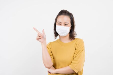 Young Asian woman wearing hygienic mask to prevent infection corona virus Air pollution pm2.5 she wearing a yellow T-shirt shoot in shot isolated on white background Banque d'images