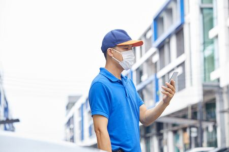 A man is holding a phone outside, wearing a mask to protect against germs and viruses. Dust prevention and prevention of toxic fumes