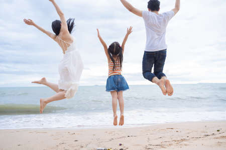 happy family jumping together on the beach Foto de archivo