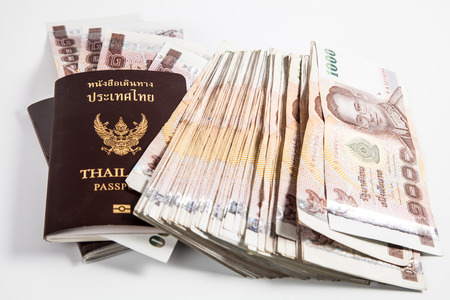Thailand passport with Thai money ready to travel isolated on white background photo