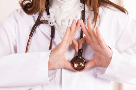 Doctor folded his hands in the shape of heart with stethoscope photo