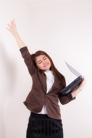 dressed for success: Photo of a young attractive and confident businesswoman, smiling with her arms in the air for winning or success. Dressed in stylish and modern business outfit.