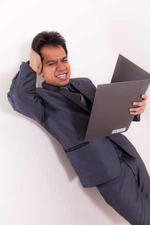 Stress Asian young Businessman With Folio photo