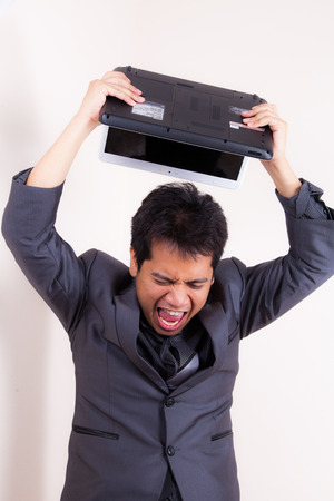 This businessman has lost his temper completely as he stand with his laptop angry and frustrated. Things are not going his way! photo
