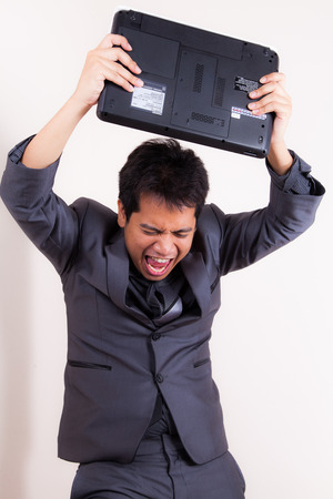 This businessman has lost his temper completely as he stand with his laptop angry and frustrated. Things are not going his way!