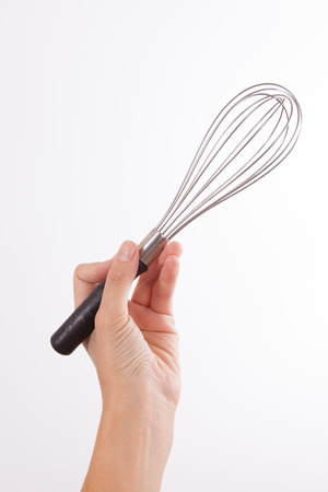 single whip: Woman Holding Egg Beater in the Air Isolated on a White Stock Photo