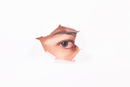 pry: A young womans eye looking through the cracked wall. Stock Photo