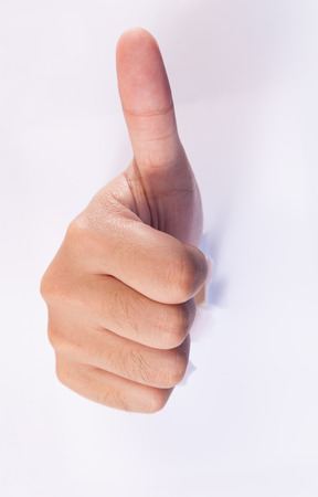Thumbs up sign from hole.