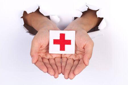 cruz roja: Bandera de la Cruz Roja Mujeres mano que sostiene aislados en blanco Foto de archivo