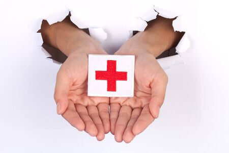 Women Hand Holding Red Cross Flag isolated on white