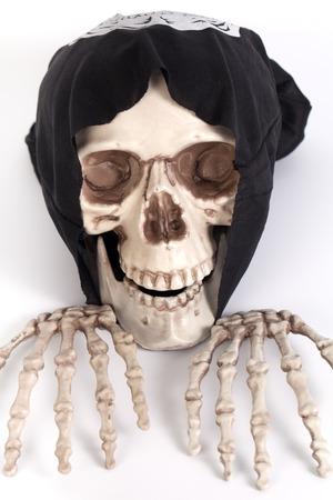 black cap: Human Skull and Human Hand with devil black cap Stock Photo