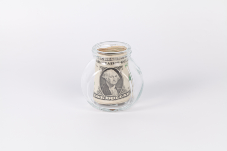 avidity: One US dollars bank notes in a glass jar isolated on white background Stock Photo