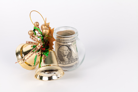 christmas debt: One dollar bills in a glass jar with golden bellin christmas time