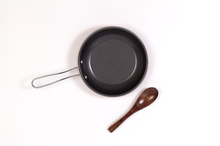 adherent: frying pan and spatula or Wooden spoon on white background