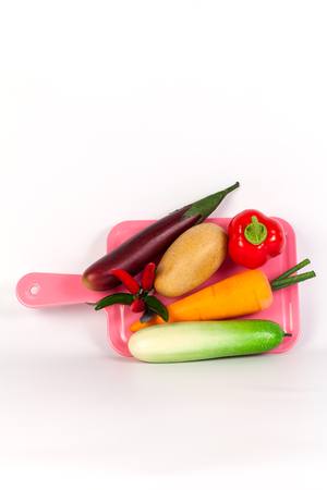 cuke: Cucumber ,Purple ,chilliEggplant ,potato,carrot and bell pepper on pink chopping block isolated on white background
