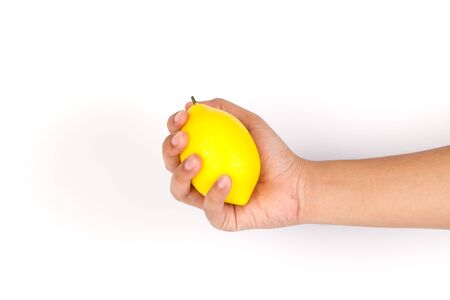 picking fingers: One young male hand holding a yellow lemon.