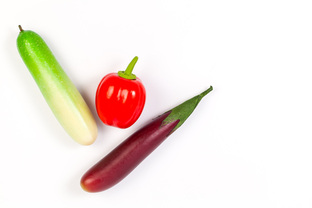 cuke: Close up of fake cucumber,Purple Eggplant and bell pepper. Isolated on a white background