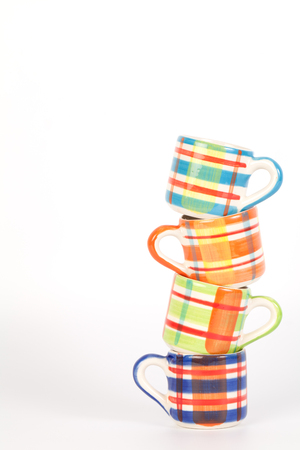 chequer: Tower of colorful   pattern cups isolated on white