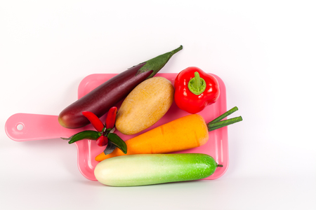 Cucumber ,Purple ,chilliEggplant ,potato,carrot and bell pepper on pink chopping block isolated on white background