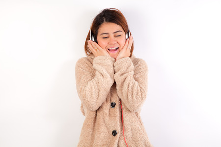 Attractive Young asian woman in Brown coat with rabbit hat,white background Imagens