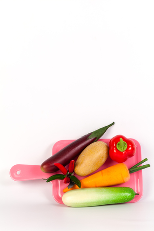 Cucumber ,Purple ,chilliEggplant ,potato,carrot and bell pepper on pink chopping block