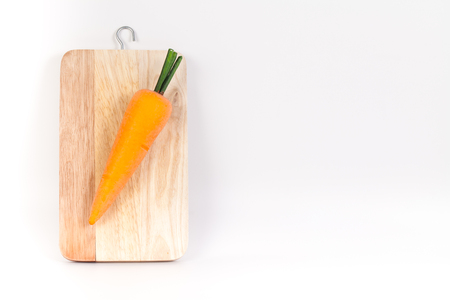 A view looking down on  an carrot on a worn butcher block cutting board isolated on white