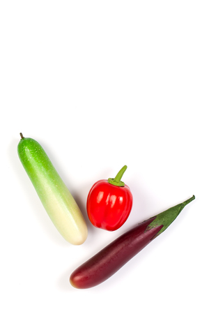 Close up of fake cucumber,Purple Eggplant and bell pepper. Isolated on a white background