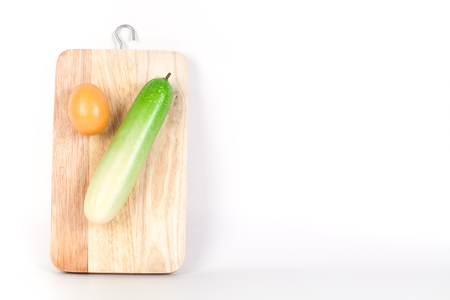 A view looking down on  an cucumber and egg on a worn butcher block cutting board. Imagens