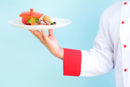 waiter serving: Chef hand hold the dish Stock Photo