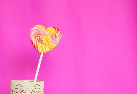 decorative shape: A heart lollipop over pink background