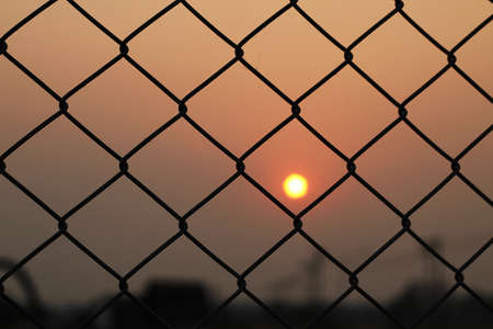 Steel mesh cage and sunset photo