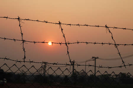Fence with a barbed wire and sunset photo