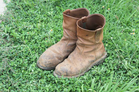 Old brown work boots on green grass photo
