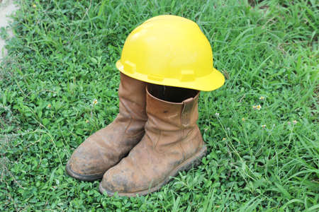 Old brown work boots and hard hat  on green grass photo
