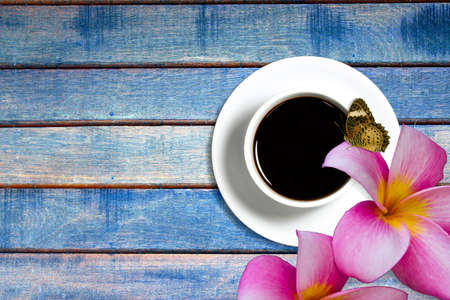 coffee cup and butterfly on wooden background