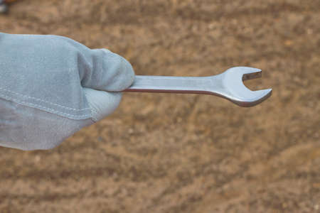 Close-up image of human hand holding wrench  Construction