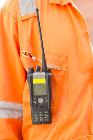 walkie talkie: Hand and walkie talkie for outdoor tank oil background