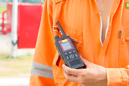 Hand and walkie talkie for outdoor tank oil background photo