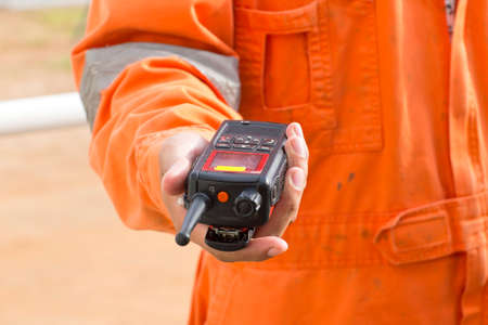 Hand and walkie talkie for outdoor tank oil background