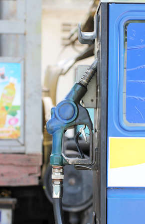fuel nozzle pumping at gas station