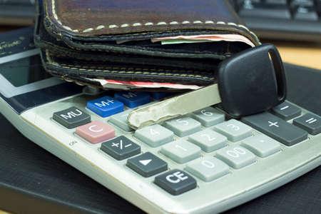 car key on calculator and money pocket