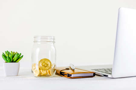 Bitcoin coin golden coin in the glass jar on wooden table ,stack of cryptocurrencies bitcoin isolated on white background,Bitcoin coin golden coin.Set of cryptocurrencies with a golden bitcoin as most important cryptocurrency concept.