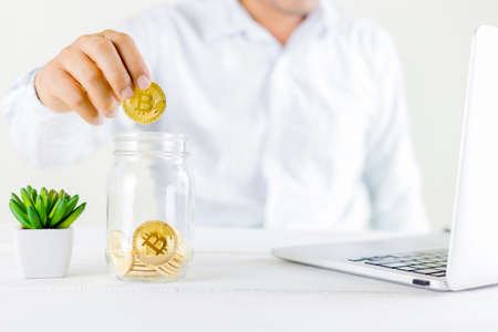Bitcoin coin golden coin in the glass jar on wooden table ,Man holding in hand symbol of crypto currency.Set of cryptocurrencies with a golden bitcoin as most important cryptocurrency concept.