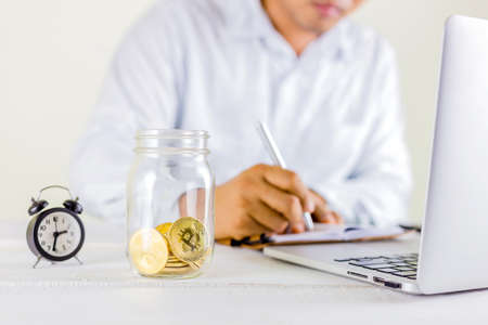 Bitcoin coin golden coin in the glass jar on wooden table ,Man record profit on notebook  for trading cryptocurrency or bitcion.Set of cryptocurrencies with a golden bitcoin as most important cryptocurrency concept.